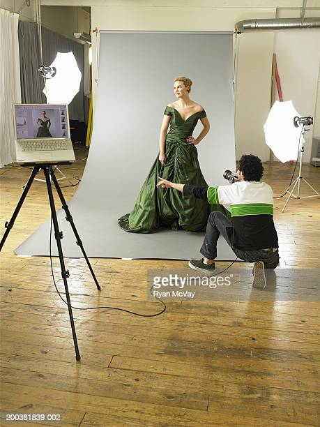 Man photographing young female model on set at photo shoot