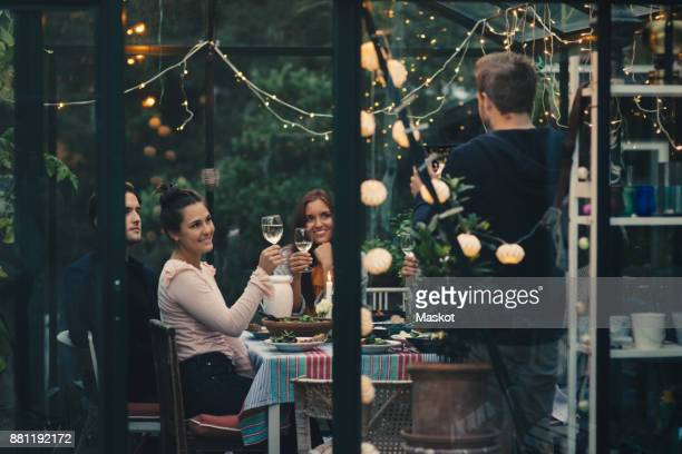 Man photographing young friends raising toast with wineglasses during dinner party