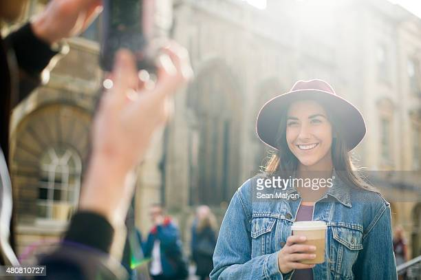 Man photographing young woman in hat