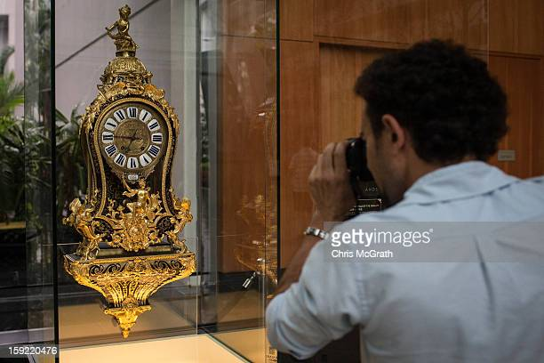 A man photographs a 1730 Boulle Marquetry Cartel clock on display January 9 2013 at Marina Bay Sands in Singapore To commemorate the Year of The...
