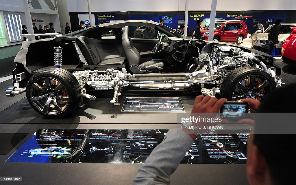 A man photographs a cross-sectioned Nissan GTR during a media preview at the Beijng Auto Show on April 23, 2010. Auto sales in booming China hit 13.64 million in 2009, overtaking the United States, as increasingly well-off Chinese consumers continued to snap up cars, helped by government incentives such as lower taxes. AFP PHOTO/Frederic J. BROWN