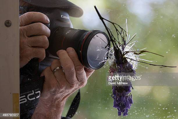 A man photographs a flowerfilled bullet hole in the windows of the IV Deli May 25 2014 in Isla Vista California According to reports 22 year old...