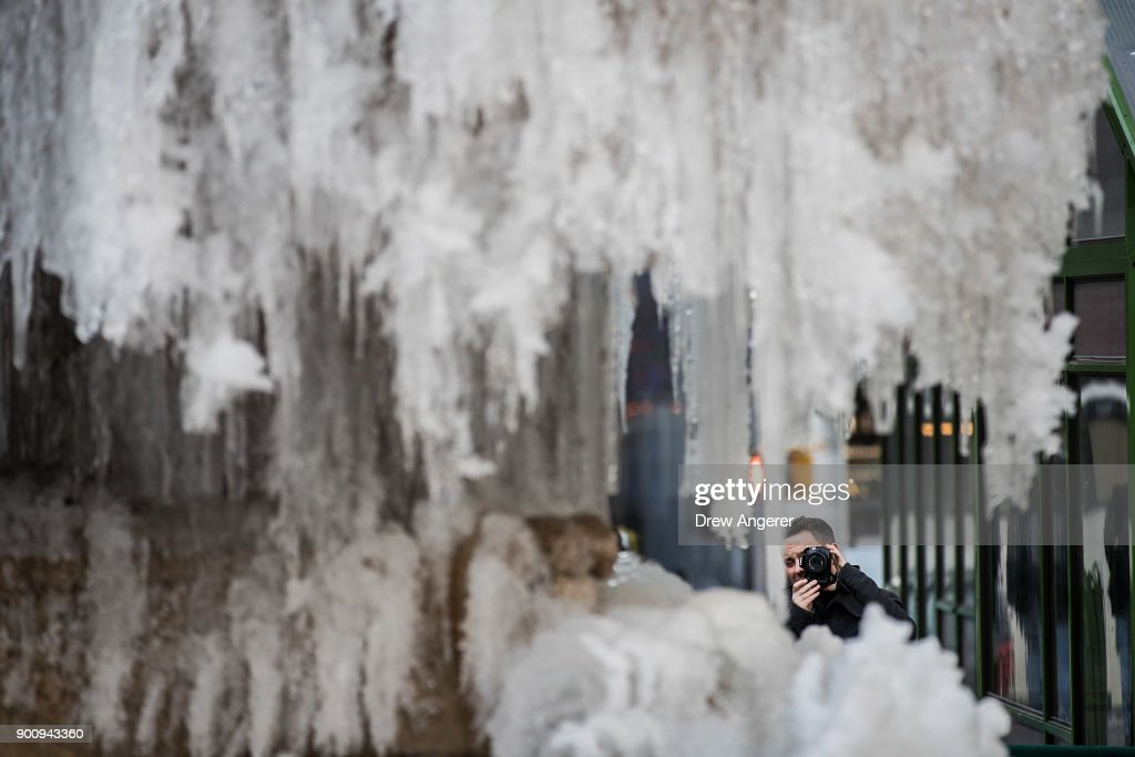 A man photographs a frozen fountain in Bryant Park, January 3, 2018 in New York City. New York City was placed under a winter storm watch Wednesday as a major weather system is expected to threaten the area with heavy snow and powerful wind Wednesday night into Thursday.