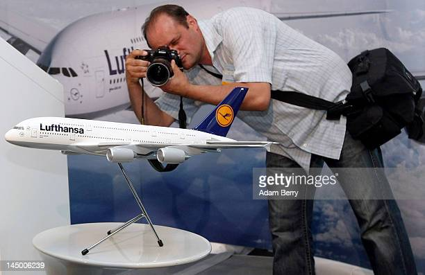 A man photographs a model of an Airbus A380 airplane to be christened 'Berlin' prior to its christening ceremony at Tegel airport on May 22 2012 in...