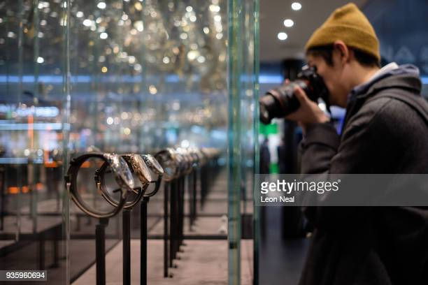 A man photographs a range of watches by Jaquet Droz at the BaselWorld watch fair on March 21 2018 in Basel Switzerland The annual watch trade fair...