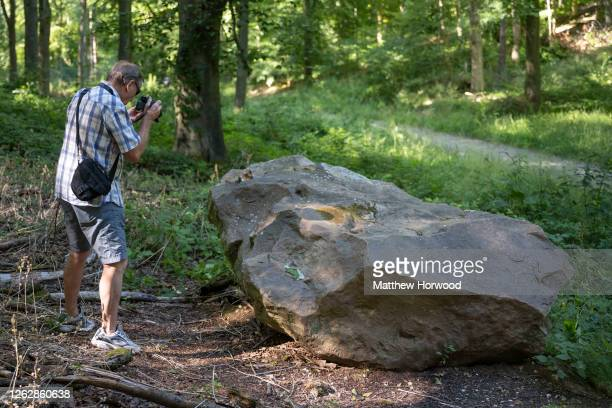 Man photographs a sarsen stone in the West Woods on July 30, 2020 in Marlborough, England. Archaeologists have discovered that the sarsen stones used...