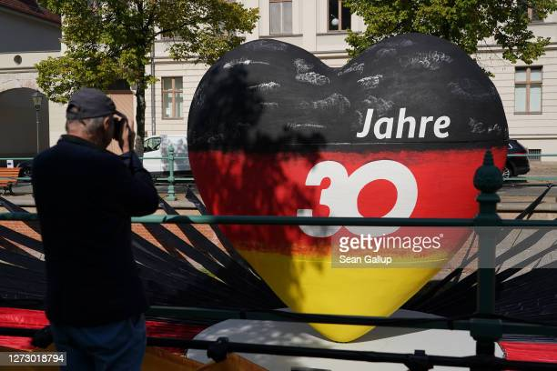 """Man photographs a sculpture of a heart in the colors of the German flag that reads: """"30 years"""" as part of an outdoor exhibition marking the upcoming..."""