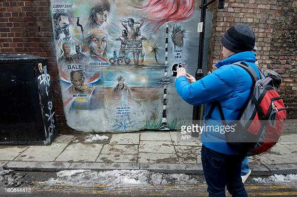 A man photographs a work of street art by Paul Don Smith during a street art tour in east London on January 22 2013 Street Art London leads visitors...