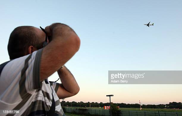 A man photographs an airplane taking off from Berlin Tegel Otto Lilienthal Airport on September 3 2011 in Berlin Germany The airport which was opened...