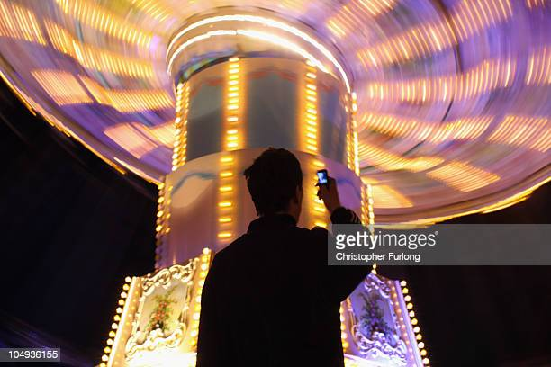 A man photographs an attraction as revellers enjoy the thrills and fun of the traditional fair ground at the annual Goose Fair on October 6 2010 in...