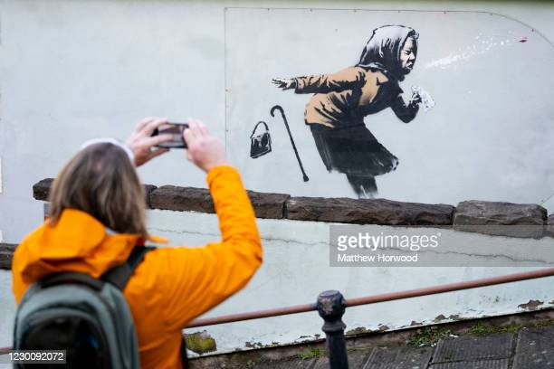 """Man photographs artwork by Banksy on December 12, 2020 in Bristol, England. Banksy claimed the artwork """"achoo"""" as his in a tweet after it appeared on..."""