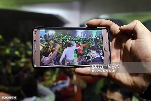 A man photographs attendees dancing during a group wedding ceremony in the rebelheld side of the northern Syrian city of Aleppo of December 9 2015 A...