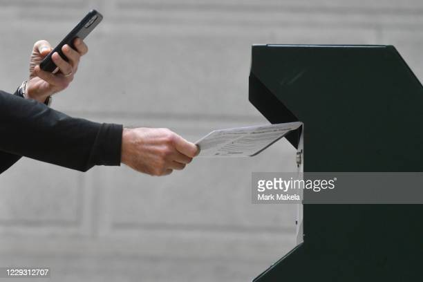 Man photographs himself depositing his ballot in an official ballot drop box while a long line of voters queue outside of Philadelphia City Hall at...
