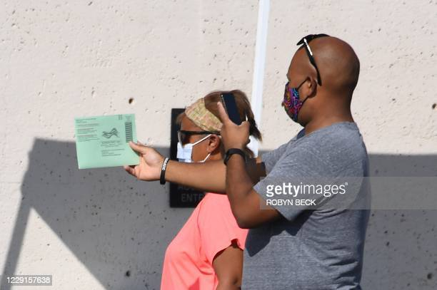 Man photographs his mail in ballot before depositing it at a ballot collection box in Phoenix, Arizona on October 18, 2020. - Arizona is one of the...