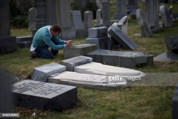 A man photographs Jewish tombstones laying vandalized at Mount Carmel Cemetery February 27 2017 in Philadelphia Pennsylvania Police are investigating...