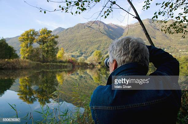A Man Photographs Scenery Across A Tranquil Lake; Locarno, Ticino, Switzerland