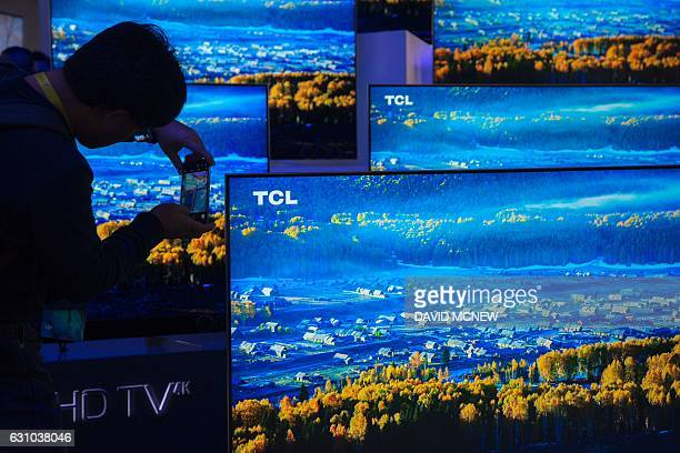 A man photographs TCL 4K UHD TVs during the 2017 Consumer Electronic Show at the Las Vegas Convention Center in Las Vegas Nevada January 5 2017 / AFP...