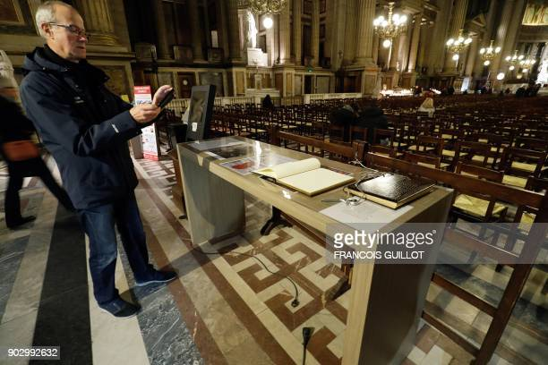 A man photographs the book of condolence for the late French musician Johnny Hallyday at La Madeleine Church in Paris on January 9 2018 French music...