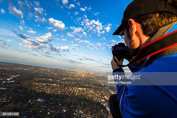 A man photographs the city from a hot air balloon