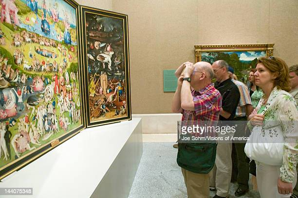 Man photographs The Garden of Earthly Delights by Hieronymus Bosch in the Museum de Prado Prado Museum Madrid Spain