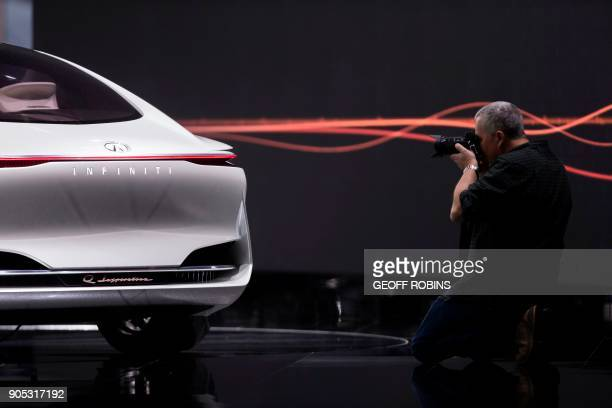 A man photographs the Infiniti Q Inspiration during the Press Preview for the 2018 North American International Auto Show in Detroit Michigan January...