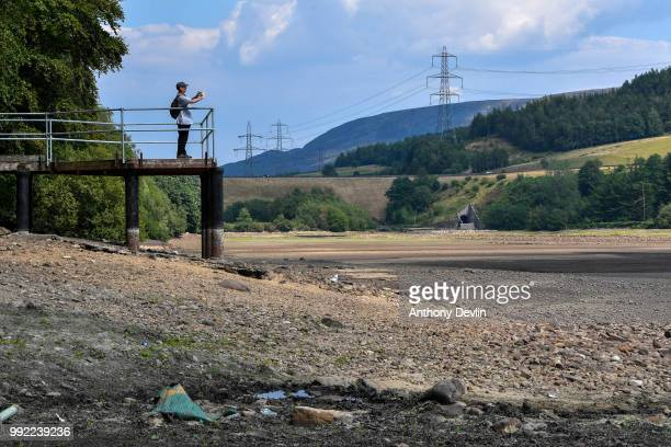 A man photographs the low water levels in Bottoms Reservoir one of the Longendale Reservoirs near Tintwistle in the High Peak on July 5 2018 in...