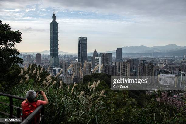 Man photographs the Taipei 101 tower, once the worlds tallest building, and the Taipei skyline from the top of Elephant Mountain on January 7, 2020...