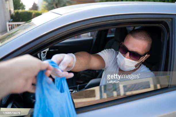 man picking his restaurant food or package from his car at a pick up curve. during pandemic - curbside pickup stock pictures, royalty-free photos & images
