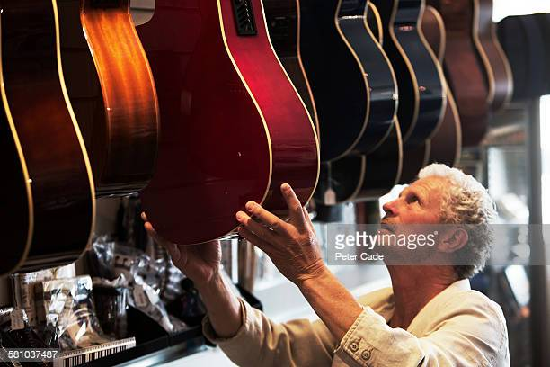 man picking out guitar in shop - hobbies stock pictures, royalty-free photos & images