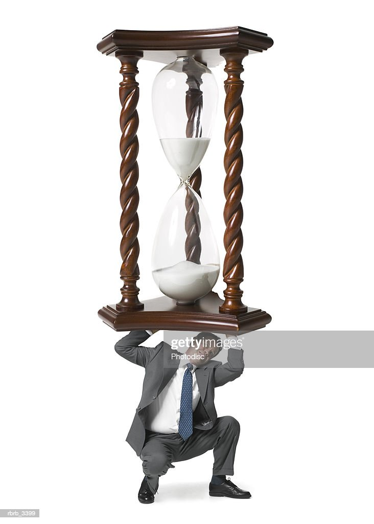 Man picking up a hourglass : Foto de stock