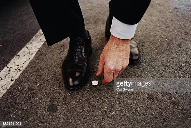 Man picking up coin from street