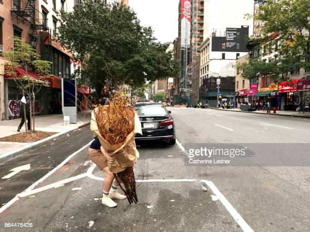 Man picking up large dried plant wrapped in brown paper on the street