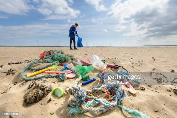 man picking up plastic pollution collected on beach, north east england, uk - environmental damage stock pictures, royalty-free photos & images