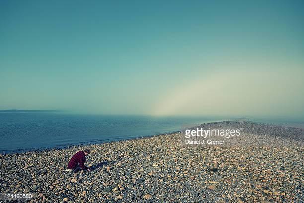 Man picking up stones near seashores