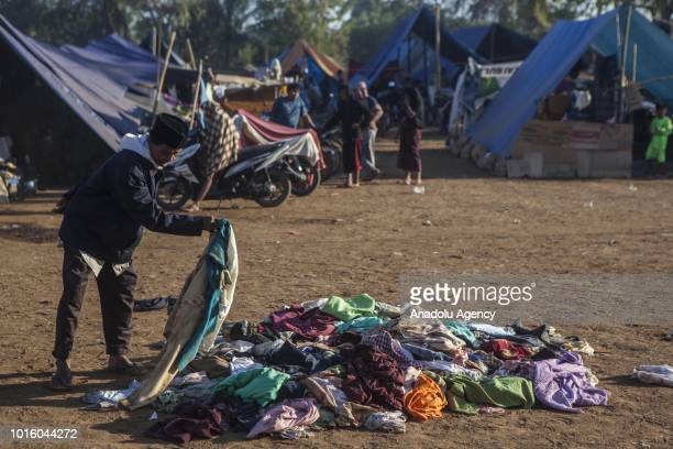A man picks clothes which are donated for people affected by earthquake at a temporary shelter in Lombok Indonesia on August 13 2018 According data...