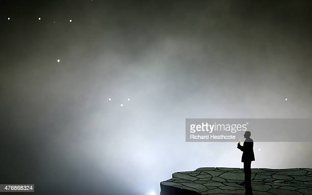 A man picks up a burning rock during the Opening Ceremony for the Baku 2015 European Games at the Olympic Stadium on June 12 2015 in Baku Azerbaijan