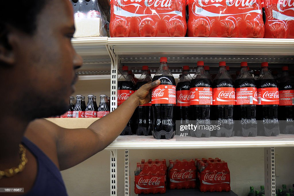 A man picks up a Coca Cola bottle in a supermarket of Fort-de-France, on March 30, 2013 in the French caribean island of La Martinique. The French national assembly on March 27, 2013 ruled to align the additional sugar rates of the products sale in the overseas territories with the mainland's rates.