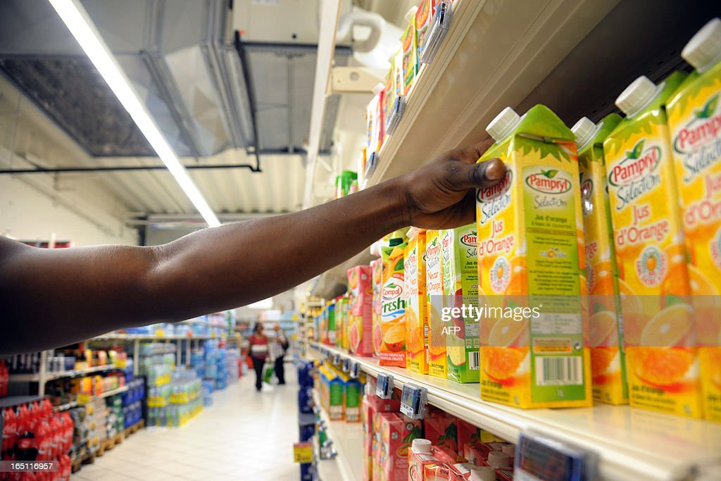 A man picks up a fruit juice bottle in a supermarket of Fort-de-France, on March 30, 2013 in the French caribean island of La Martinique. The French national assembly on March 27, 2013 ruled to align the additional sugar rates of the products sale in the overseas territories with the mainland's rates.