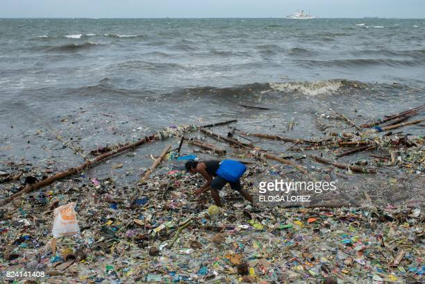 A man picks up garbage washed ashore at Manila Bay on July 29 2017 after Typhoon Nesat hit the Philippines