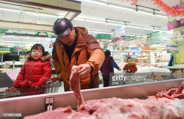 A man picks up meat at a supermarket in Hangzhou China's Zhejiang province on January 10 2019 / China OUT