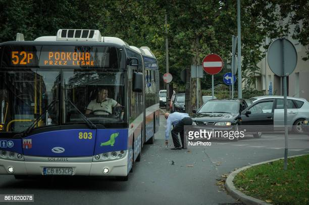 Man picks up pieces from his car after a crash with a passenger bus in Bydgoszcz, Poland on October 14, 2017.