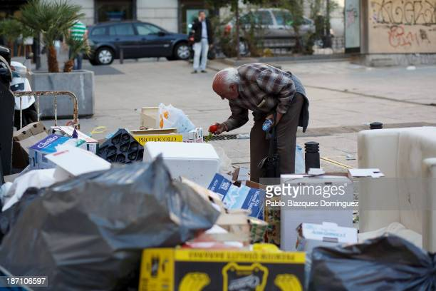 A man picks vegetables from garbage dumped around rubbish bins in the street on November 6 2013 in Madrid Spain Street cleaners garbage collectors...