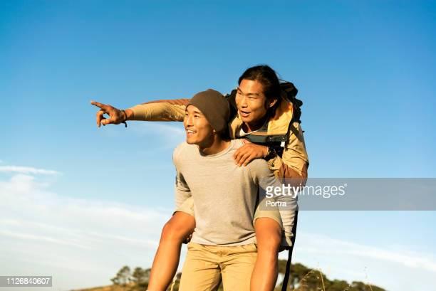 晴れた日に空に対する男ピギーバック友人 - 若い男性だけ ストックフォトと画像