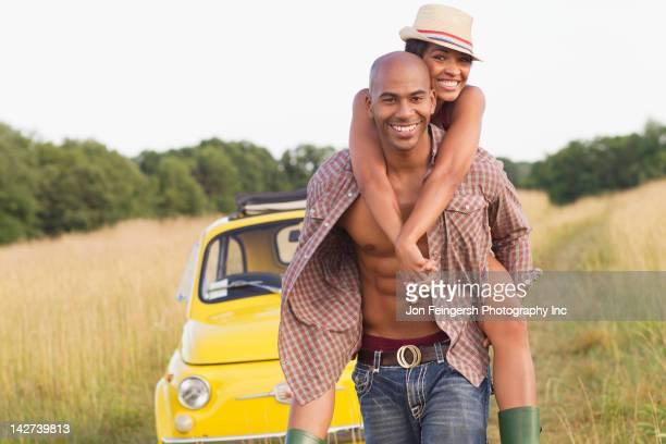 man piggybacking wife in field near car - helemaal losgeknoopt stockfoto's en -beelden
