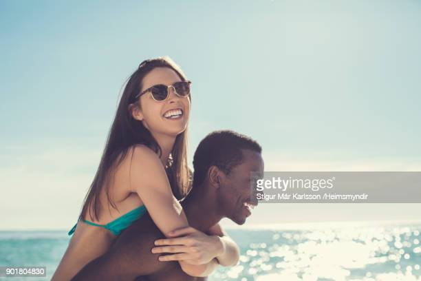 man piggybacking woman against sea during summer - three quarter length stock pictures, royalty-free photos & images