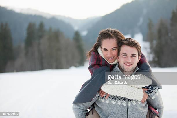 Man piggybacking woman in snow