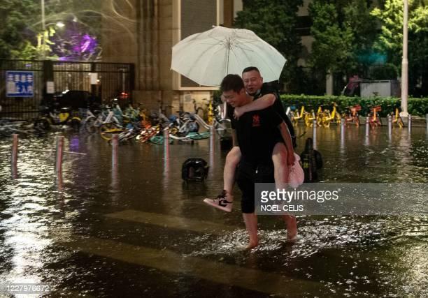 Man piggybacks a friend as they cross a flood after a sudden rain in Beijing on August 9, 2020.