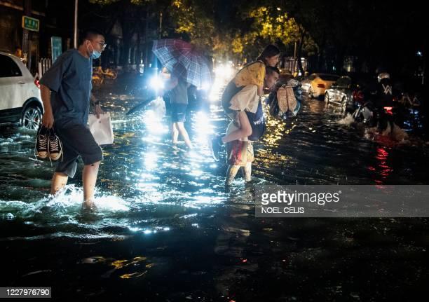 Man piggybacks a woman to cross a flooded street after a sudden rain in Beijing on August 9, 2020.