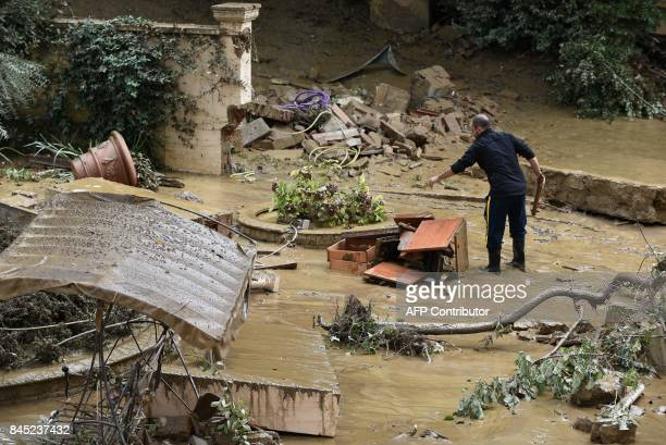 A man piles wrecked furniture outside his home in the Livorno area flooded after heavy rain on September 10 2017 At least six people have died in...