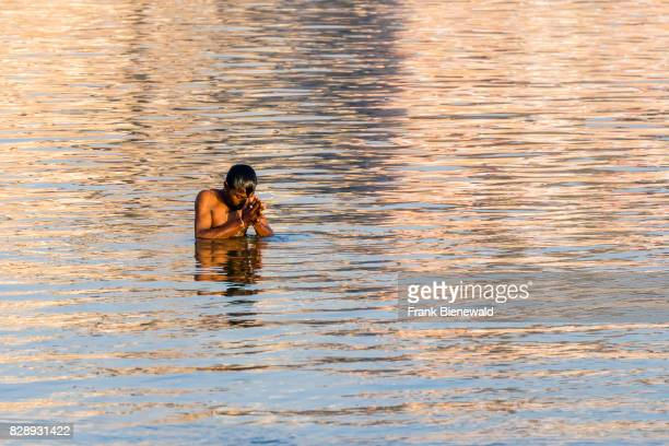 A man pilgrim is taking bath and praying on the sand banks at the holy river Ganges